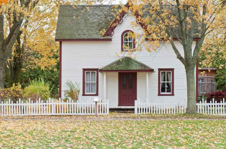 white and red wooden house with fence