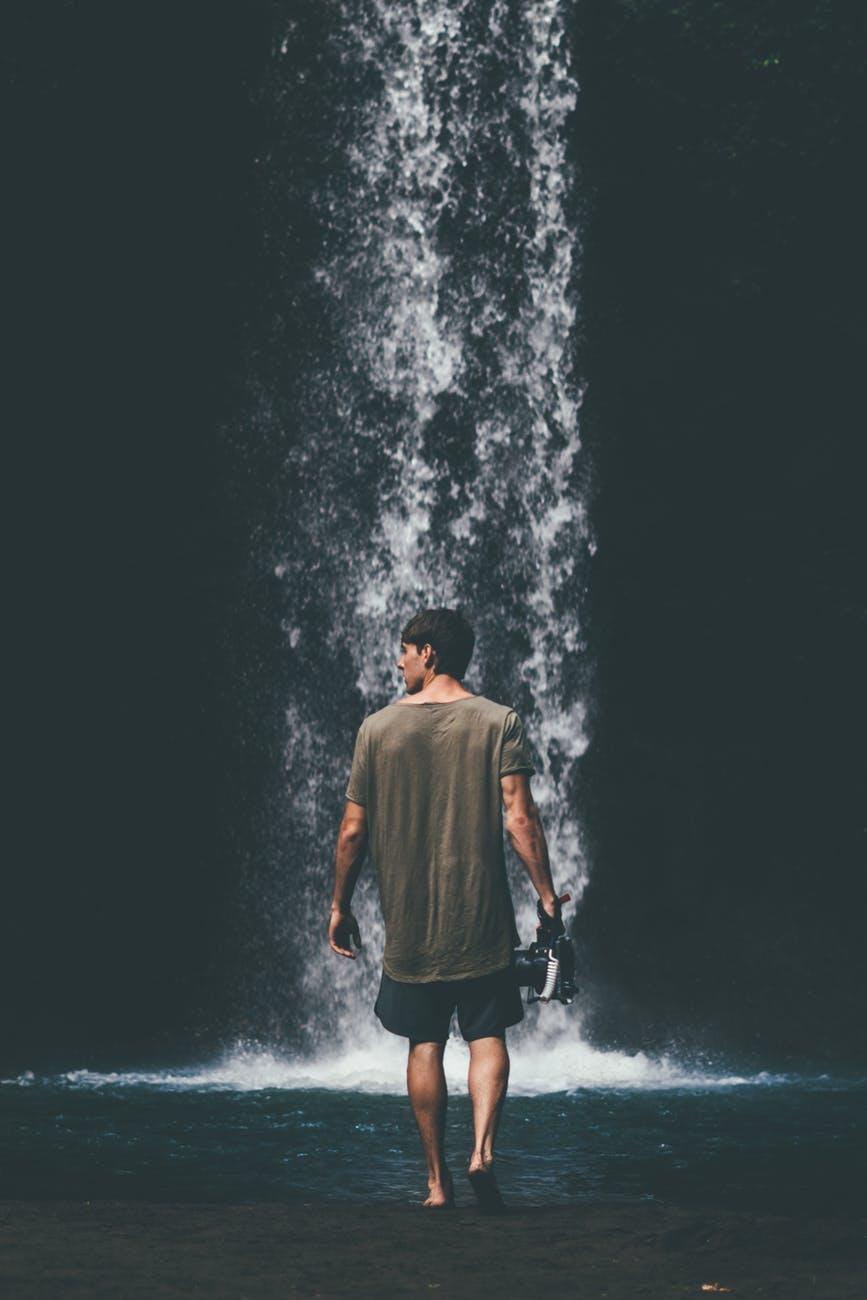 man wearing gray shirt walking near waterfalls