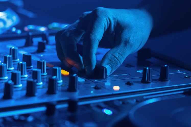 person adjusting audio of a sound mixer
