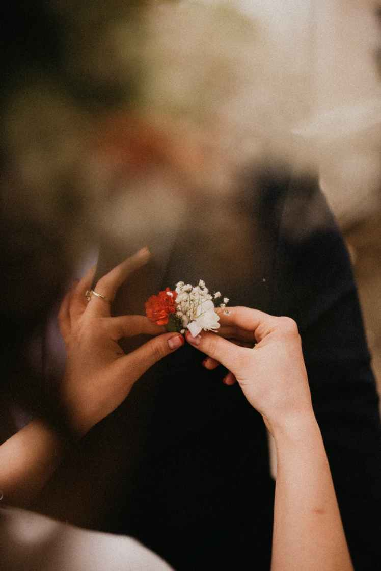 person holding white and red flowers