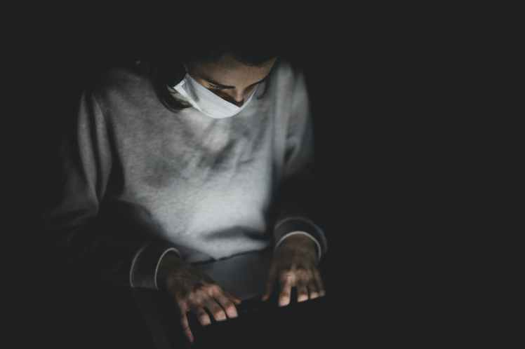 man with face mask using laptop in the dark